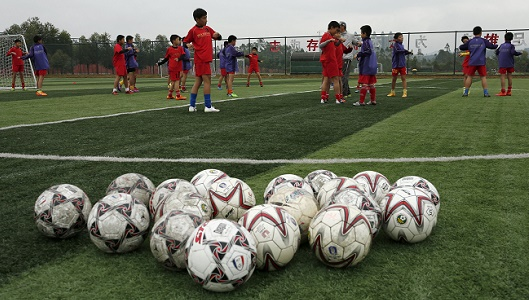 Students warm up before a training session at Evergrande soccer academy in Qingyuan, southern China